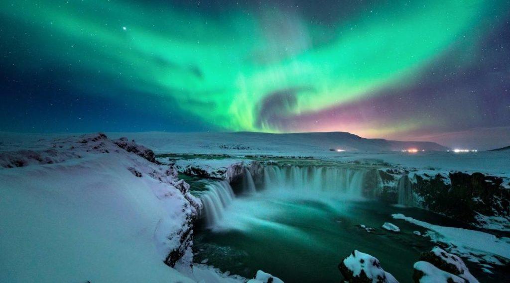 Foto de uma aurora boreal na Islândia tirada sobre as quedas de Gullfoss