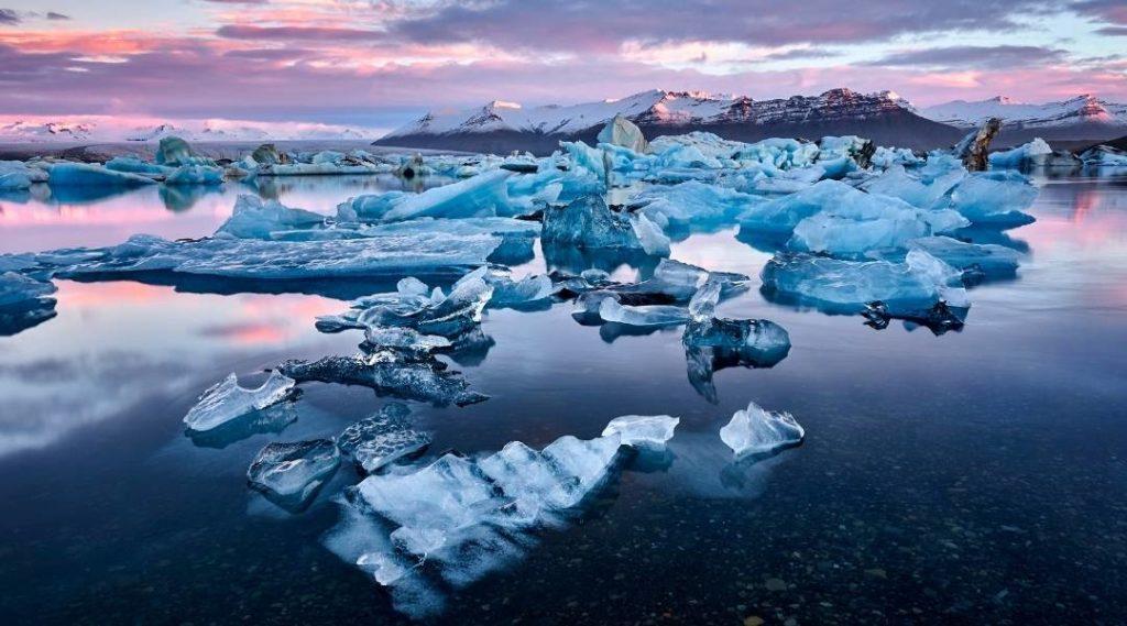Foto de icerbergs na Islândia no pôr do sol, no fundo montanhas